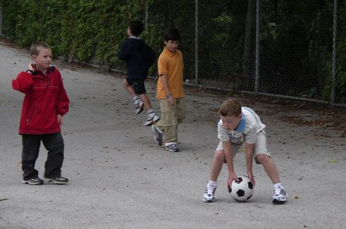 Boy in white shirt and shorts bending down to pick up soccer ball in schoolyard with another boy in a red jacket and another boy in an orange short walking up to him