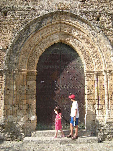 Little girl in pink dress and taller boy in white shirt and red cap looking at the portale of the Chiesa di San Francesco d'Assisi, Gerace, Calabria