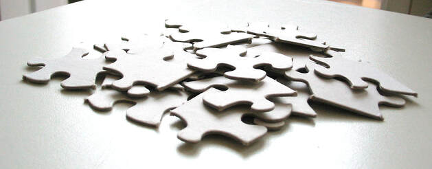 White puzzle pieces piled on white table