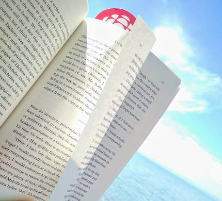 Open book page against background of blue sky, clouds, and a lake